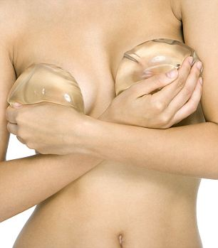Nude woman covering breasts with breast implants, cropped view --- Image by © Alix Minde/PhotoAlto/Corbis